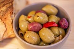 橄榄被充塞的,红辣椒和家制面包 在一个小碗的多彩多姿的橄榄在一张木桌上 免版税库存图片
