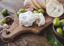 绿橄榄,被切的ciabatta,在一个木板的希腊白软干酪 香料 大蒜 免版税图库摄影