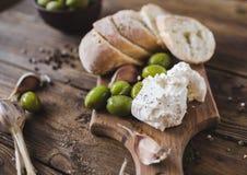 绿橄榄,被切的ciabatta,在一个木板的希腊白软干酪 香料 大蒜 Chees希脂乳 Ciabatta 在木背景的橄榄 免版税库存图片
