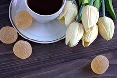 橘子果酱和一杯咖啡与黄色郁金香花束的在棕色木背景的 咖啡停留 图库摄影