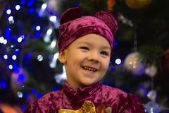 橘子果酱熊 情感男孩在一套紫色熊服装的三岁在一个新年树和蓝色灯笼的背景 库存照片
