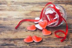 橘子果酱糖果在玻璃瓶子的形状心脏有丝带的 免版税库存照片