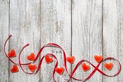 橘子果酱糖果形状心脏和红色丝带在木桌,情人节构成,贺卡上 免版税图库摄影