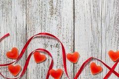 橘子果酱糖果形状心脏和红色丝带在木桌,情人节构成,贺卡上 库存照片