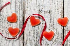 橘子果酱糖果形状心脏和红色丝带在木桌,情人节构成,贺卡上 免版税库存图片