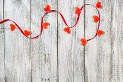 橘子果酱糖果形状心脏和红色丝带在木桌,情人节构成,贺卡上 免版税库存照片
