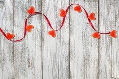 橘子果酱糖果形状心脏和红色丝带在木桌,情人节构成,贺卡上 库存图片