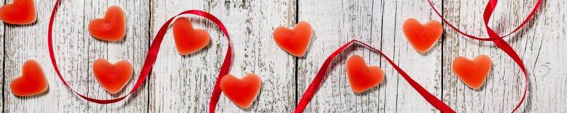 橘子果酱糖果形状心脏和红色丝带横幅在木桌,情人节构成,贺卡上 免版税库存照片
