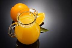 橙汁和果子在黑色 库存照片