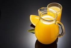 橙汁和果子在黑色 图库摄影
