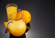 橙汁和果子在黑色 免版税图库摄影
