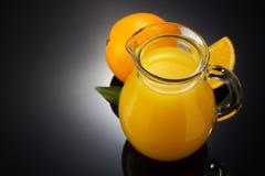 橙汁和果子在黑色 免版税库存照片