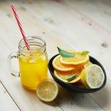 橙汁和柠檬橙色叶子柑橘在一个黑碗 免版税库存照片