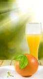 橙汁和桔子在一张木桌上 免版税图库摄影