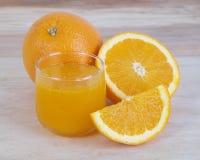 橙汁和橙色果子在木背景 免版税库存图片