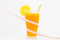 橙汁和测量的磁带,饮食概念 免版税图库摄影