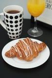 橙汁在黑表上的早餐早晨Isoalted咖啡和新月形面包白色巧克力玻璃  免版税库存图片