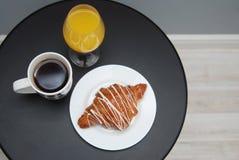 橙汁在黑表上的早餐早晨Isoalted咖啡和新月形面包白色巧克力玻璃  库存照片