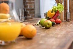 橙汁选择聚焦在玻璃水罐、新鲜的水果和蔬菜的 免版税库存照片