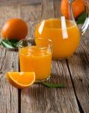 橙汁玻璃和新鲜的桔子与叶子 库存图片