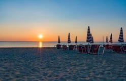 橙红在海滩的日落日出与遮阳伞和deckchair 免版税库存图片