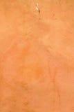 橙红色破裂的灰泥墙壁纹理背景 免版税库存照片