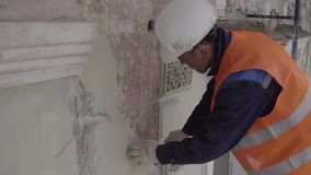 橙色一致的命中的建筑工人与白色墙壁的锤子零件 股票录像