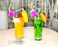 橙色两个用秸杆和装饰品装饰的鸡尾酒和绿色 免版税库存照片