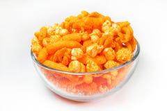 橙色乳酪吹和玉米花快餐背景 库存图片