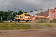橙色俄国人Mi8直升机在草草坪登陆。 图库摄影