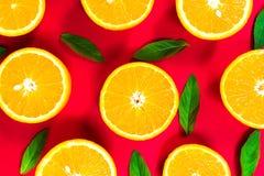 橙色切片和薄荷叶的五颜六色的图片在红色背景 r 免版税库存照片