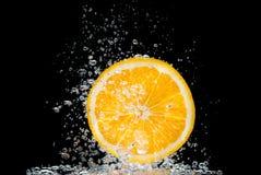 橙色切片在与泡影的水中 免版税库存图片