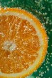 橙色切片在与泡影的水中 库存图片