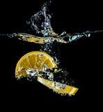 橙色切片落入水特写镜头的,宏指令,飞溅,黑背景 库存照片