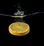 橙色切片落入水特写镜头的,宏指令,飞溅,黑背景 免版税图库摄影
