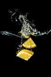 橙色切片落入水特写镜头的,宏指令,飞溅,黑背景 免版税库存照片