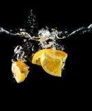 橙色切片落入水特写镜头的,宏指令,飞溅,黑背景 免版税库存图片