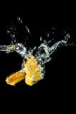 橙色切片落入水特写镜头的,宏指令,飞溅水,泡影,黑背景 库存图片