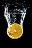 橙色切片落入水特写镜头的,宏指令,飞溅水,泡影,黑背景 图库摄影