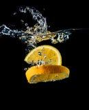 橙色切片落入水特写镜头的,宏指令,飞溅水,泡影,黑背景 免版税图库摄影