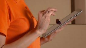 橙色制服的女性仓库工作者使用她的反对棕色纸盒的片剂计算机堆积背景 4K关闭  股票视频