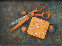 橙色剪刀大号在有一个方形的拨号盘的橙色时钟旁边在生锈的背景,内部12月的现代设计 库存图片
