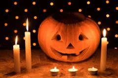 橙色南瓜作为有被雕刻的眼睛的一个头和与candl的微笑 库存照片