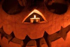 橙色南瓜作为有被雕刻的眼睛的一个头和与candl的微笑 免版税图库摄影