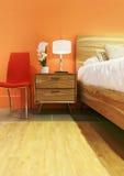橙色口气的明亮的卧室 免版税库存照片