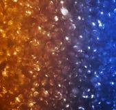 橙色和蓝色bokeh闪闪发光 免版税库存图片
