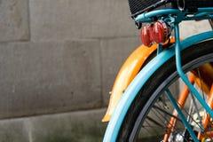 橙色和蓝色bycicle后面轮子与混凝土墙设计减速火箭的行家的 免版税库存照片