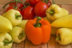 橙色和青椒用蕃茄在一木surfac分支 免版税库存照片