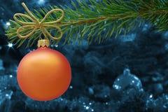 橙色圣诞节中看不中用的物品和一个云杉的分支 免版税库存图片