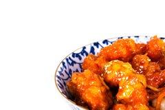 橙色在一个蓝色和白色样式碗的鸡中国食物在与文本空间的白色背景 图库摄影